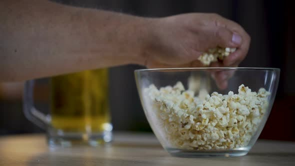 Thumbnail for Man eating popcorn and drinking a beer while watching movie at home, close-up