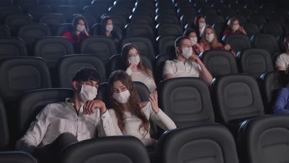Couple Wearing Face Masks Talking in Cinema.
