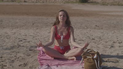 Long Haired Woman in Red Sexy Bikini Meditates on Sand Beach