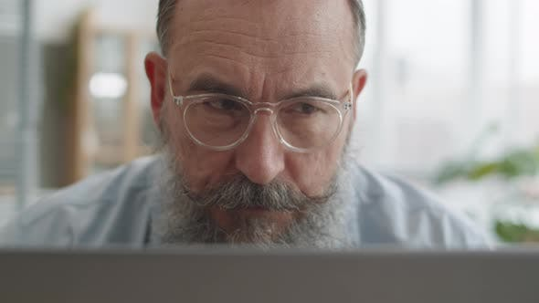 Thumbnail for Senior Man Looking at Laptop Carefully
