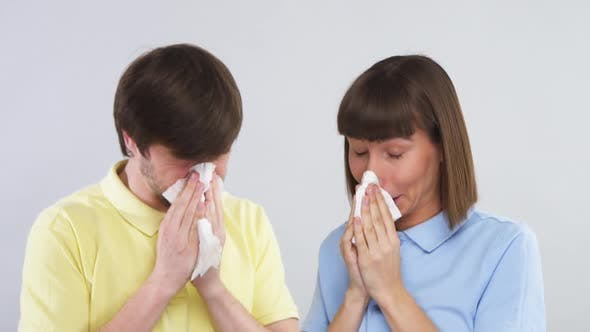 Thumbnail for Happy Couple with Tissue in Arms Smiling After Blowing Their Noses and Looking at Each Other with
