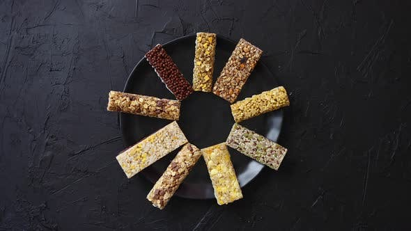 Thumbnail for Different Kind of Granola Fitness Bars Placed on Black Ceramic Plate on a Table