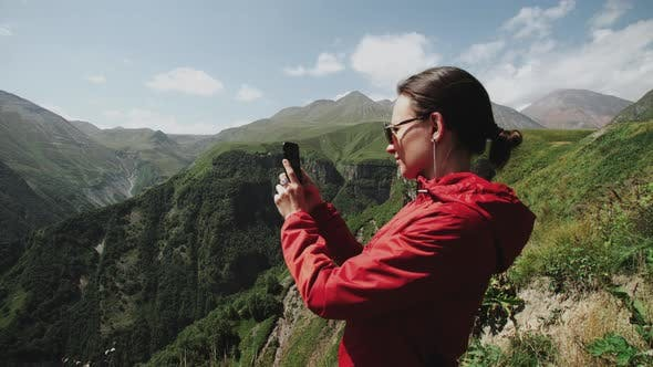 Cover Image for Woman Travel on the Edge of Cliff Over Mountain Gorge. Makes Photo of Alpine Landscape on Smartphone