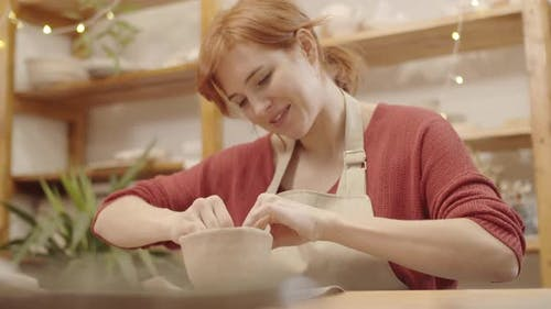 Young Woman Sculpting Earthenware Vessel in Pottery Workshop