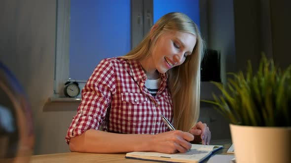 Cheerful Female Writing in Daily Planner. Lively Young Blond Woman in Casual Checkered Shirt Sitting