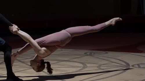 Jeune femme est faire une scission alors qu'un homme tient son duo gymnastique
