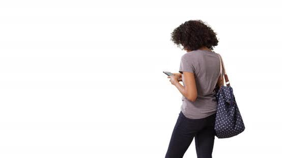 Thumbnail for Rear view of black female looking around anxiously, texting on phone in studio
