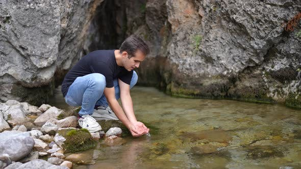 Young Man Relaxing on the Rock By River in the