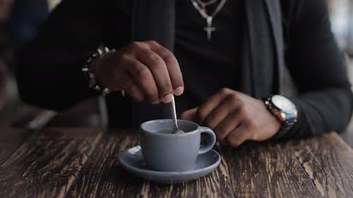 African American Man Mixing Sugar in a Tea Cup