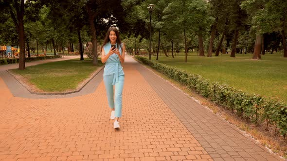 Thumbnail for Young Caucasian Woman Happy About Great News Walking on the Street in City Park