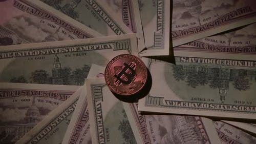 Bitcoin Lies on a Table on Paper Bills