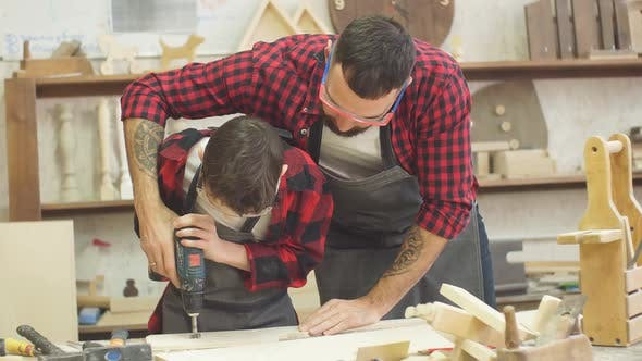 Thumbnail for Handsome Father and His Teen Son Working with Drill at Workshop