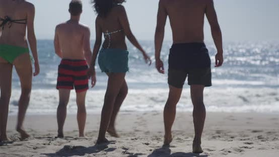 Young hipster group of interracial friends wandering the beach