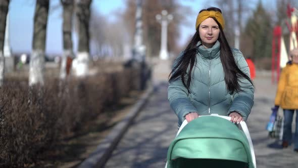 Thumbnail for Woman Walking Through the Park with a Pram