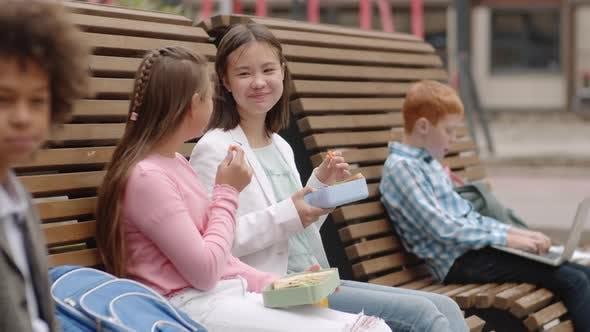 Two Schoolgirls Having Bite Together Outdoors