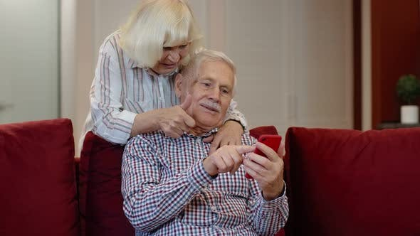 Thumbnail for Senior Old Couple Grandparents Talking and Using Mobile Phone Computer at Home. Internet Shopping