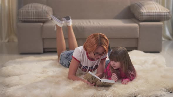 Thumbnail for Mom Reads the Girl a Book. Portrait Beautiful Mother and Cute Little Daughter