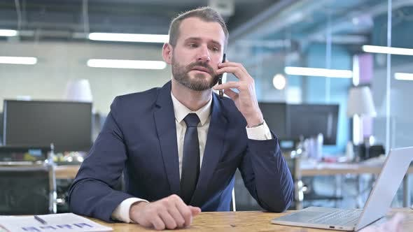 Thumbnail for Cheerful Businessman Talking on Smartphone in Office