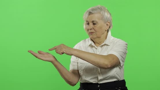 Thumbnail for An Elderly Woman Points at Something and Smiles. Old Grandmother. Chroma Key