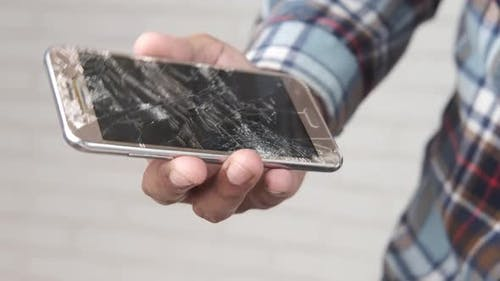 Close Up of Man Hand Holding Broken Smart Phone