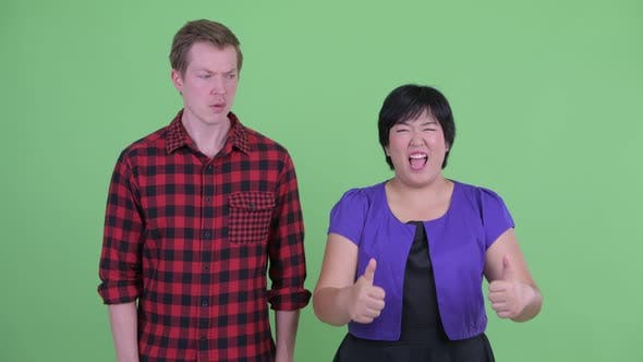 Thumbnail for Happy Overweight Asian Woman Giving Thumbs Up with Scandinavian Hipster Man Looking Confused