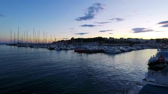 Thumbnail for Seehafen mit Booten und Gebäuden im Hintergrund - Sonnenuntergang