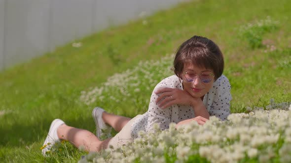 Woman with Colorful Sunglasses Lays on Lawn in Urban Park and Enjoys Flowers