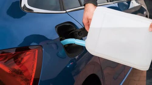 Close Up Man Filling a Diesel Engine or Exhaust Fluid DEF From Canister Into the Tank of Blue Car.