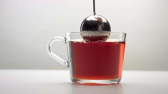 Slow Motion of an Intensive Movement of the Infuser Spoon with Tea in Cup
