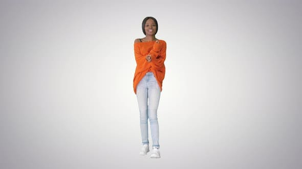 Young Casual African Woman Dancing on Gradient Background