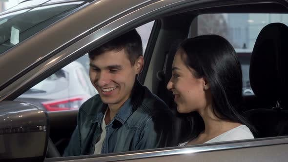 Young Happy Couple Choosing New Automobile at Dealership Salon