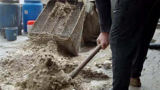 Worker Throws Sand with a Shovel Into the Cement Machine