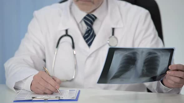 Pulmonologist Looking at X-Ray of Lungs and Prescribing Treatment to Patient