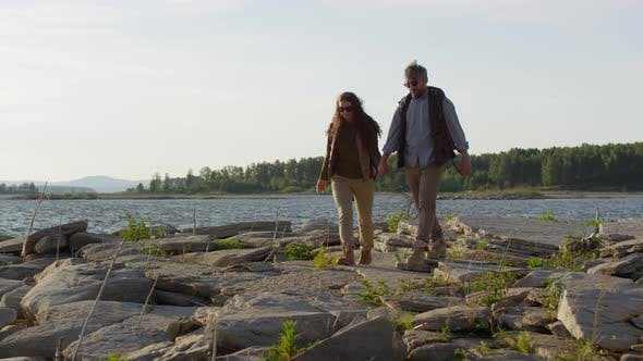 Thumbnail for Tourist Couple Holding Hands and Walking on Rocky Lakeshore