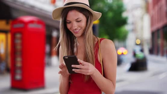 Thumbnail for Hipster girl in her 20s messaging on smartphone outside in London street