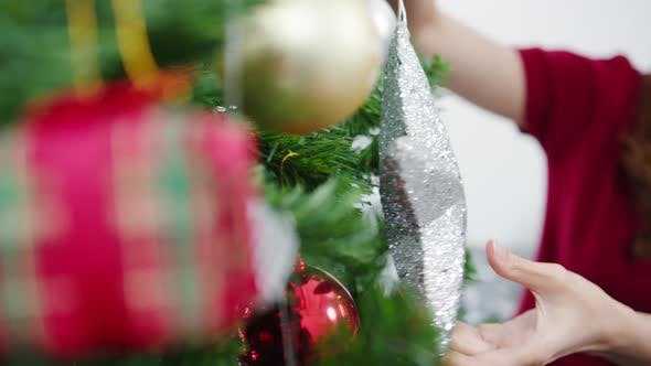Asian female decorated with ornament on Christmas tree at Christmas and New Year festival