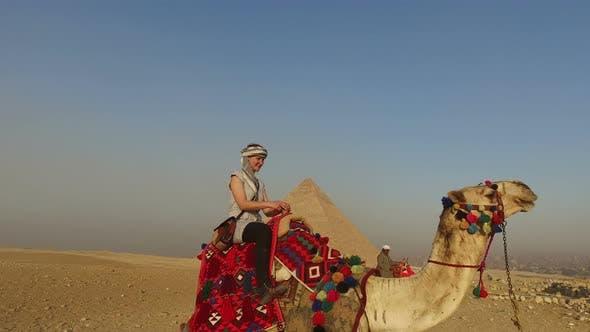 Young woman sitting on a camel at Giza pyramids