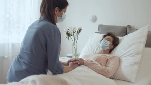 Home Caregiver With Face Mask Comforting Female Senior Patient Lying in Bed at Nursing Home