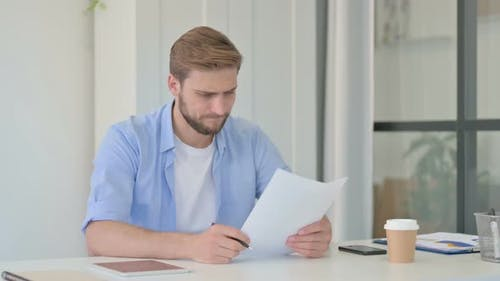 Young Creative Man Reacting to Loss While Reading Documents