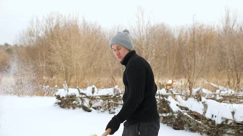 Young Man Throwing Snow with Yellow Plastic Shovel