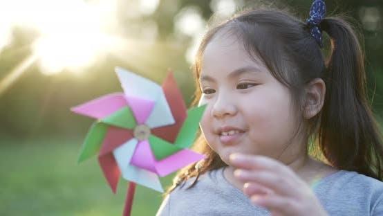 Fille asiatique drôle avec moulin à vent coloré dans le jardin