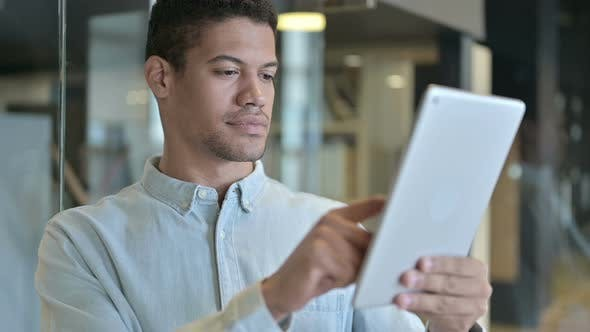 Thumbnail for Young African Man Using Tablet in Modern Office
