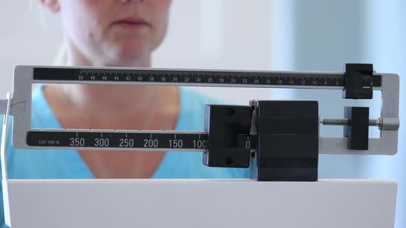 Thumbnail for Woman weighing herself on scale