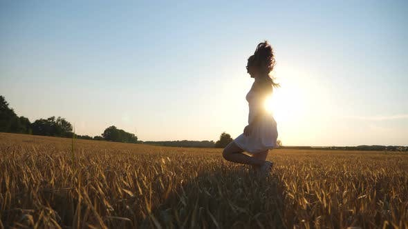 Thumbnail for Unrecognizable Woman in White Dress Running Through Field with Yellow Wheat at Sunset