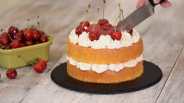 Cover Image for Woman Is Cutting The Naked Cherry Cake With Vanilla Cream