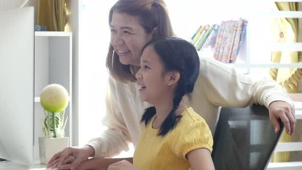 Nahaufnahme Schönes asiatisches Mädchen, das Computer mit ihrer Mutter zusammen benutzt