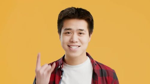 Cheerful Asian Guy Gesturing Rock Sign Posing Over Yellow Background