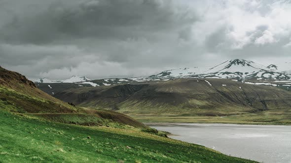 Thumbnail for Moving Clouds Over Snow Mountains And Arctic Sea Fjord And Fresh Green Grass In Iceland