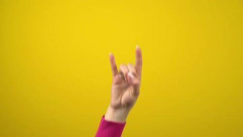 Female Hand Shows the Sign of the Horns. Studio Photography on an Isolated Yellow Background
