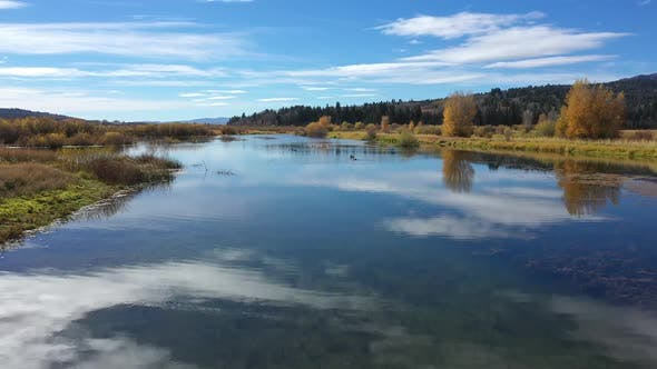 Flying low over glassy pond in Wyoming